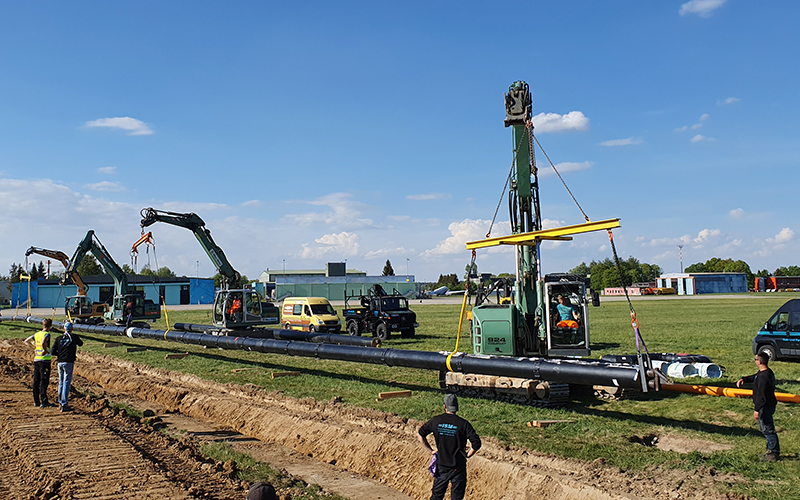 Excavation work for district heating grid. The image detail shows four excavators and multiple workers.