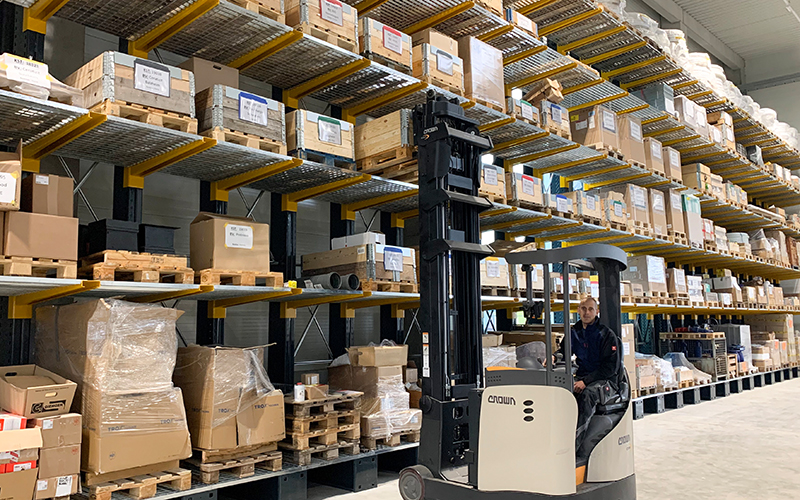 Alois Müller Group warehouse. Forklift operator in the foreground of shelves